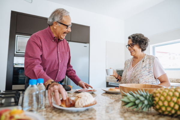 an older adult couple sit at their kitchen island eating breakfast