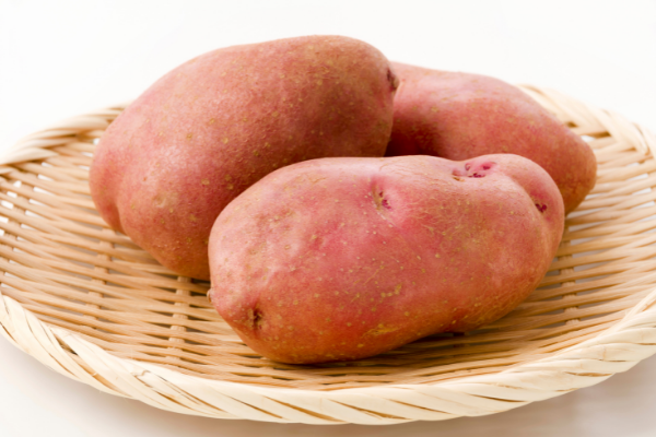 three whole red skinned potatoes sit on a wicker plate