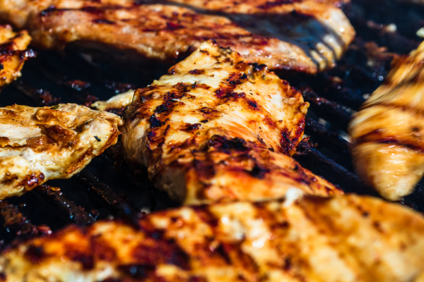 chicken with nice grill marks being turned on a grill