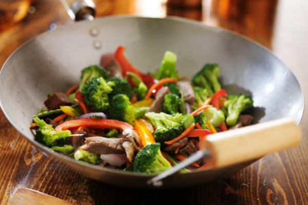 a vegetable stir fry being prepared in a wok including broccoli, red and yellow peppers and onions