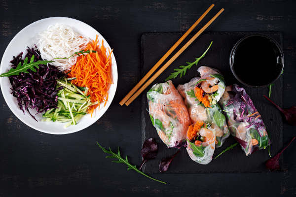 a bowl of sliced julienne vegetables next to a plate of rice paper rolls on a black slate board with chopsticks