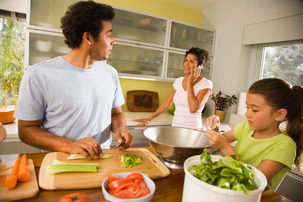 a family preparing salad together in the kitchen