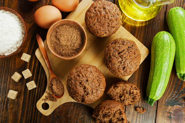 zucchini muffins sitting on a white cutting board with eggs and raw zucchini around them