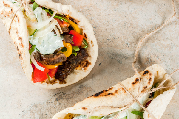 greek steak wraps with vegetables and tzatziki wrapped in bread