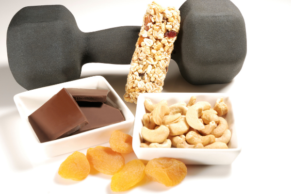 post workout recovery foods including dried fruit, nuts, granola bar and dark chocolate with a hand weight