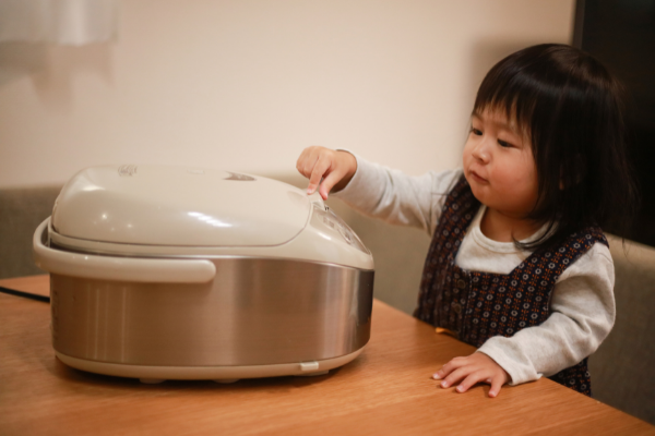 a young girl pushes buttons on a stainless steel rice cooker