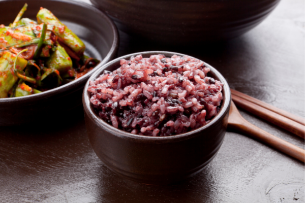 a bowl of cooked black rice that is a beautiful purple color in a black bowl