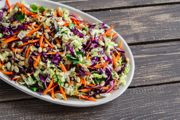 a round white bowll filled colorful red, green and orange coleslaw with edamame beans