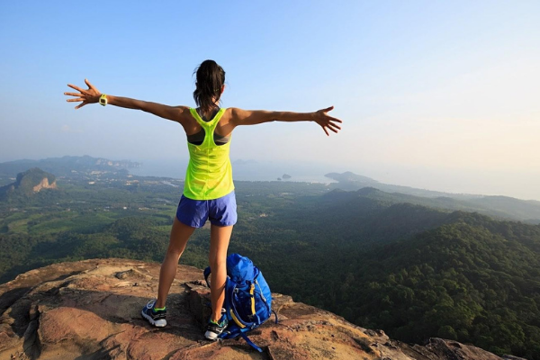 A fit woman in short blue shorts and a yellow tank top does a mountain stretch with her arms wide on top of a mountain