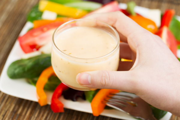 a woman holding a cup of salad dressing about to pour it over a salad