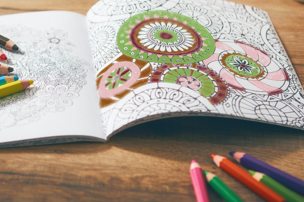 a partially completed mandala pattern picture in a coloring book next to colored pencils