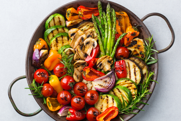 a round platter filled with artistically arranged roasted vegetables including tomatoes, carrots, asparagus and onion