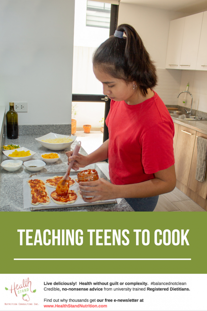 A young girl wearing a pink tshirt spreads sauce on mini pizzas in the kitchen