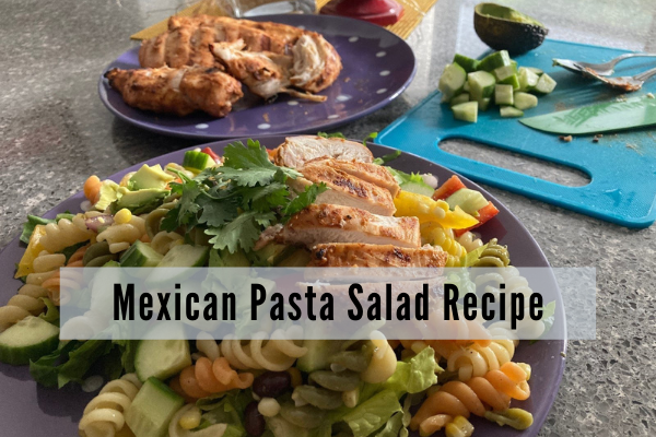 a dinner plate piled with lettuce, pasta, corn, avocado and tomatoes topped with grilled chicken. a plate of grilled chicken sits in the background