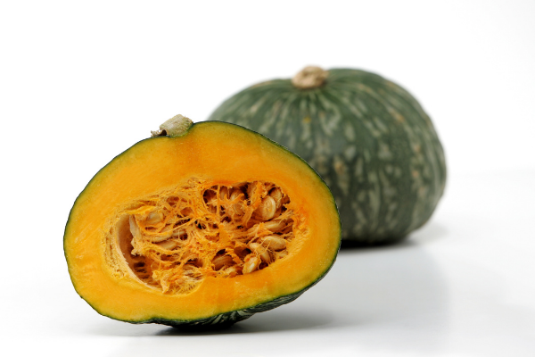 Two kabocha squash, one cut in half and one whole. the outer flesh is dark green and specked tan and the interior is bright orange thick flesh and large seeds like a pumpkin