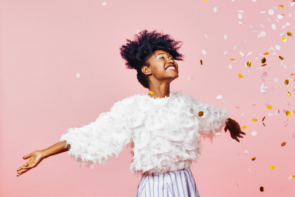 an african american woman in a white frilled top and blue skirt dancing joyfully in front of a pink wall