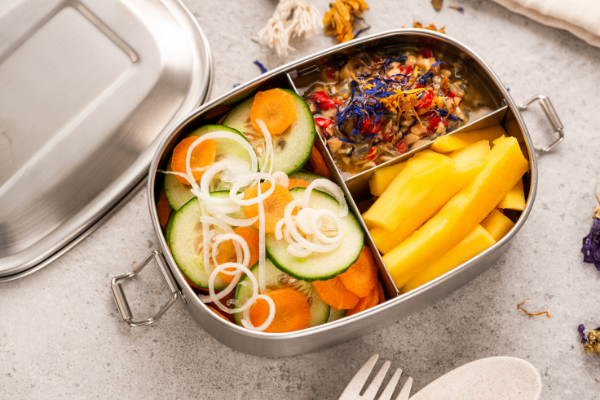 A summery looking bento box with a sandwich, slices of mango and berries with granola
