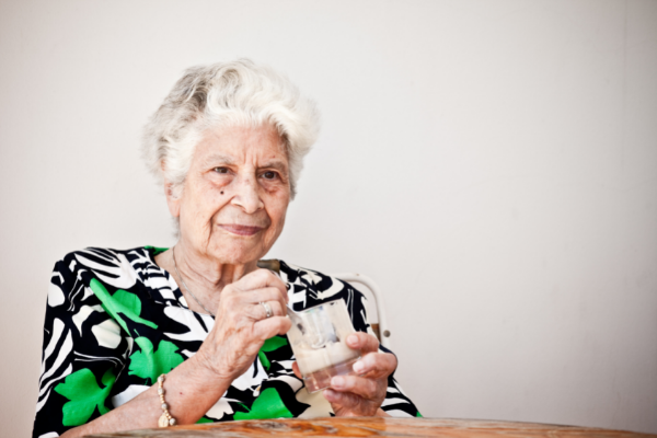 An older woman with short white hair and a green floral shirt eats ice cream from a glass cup