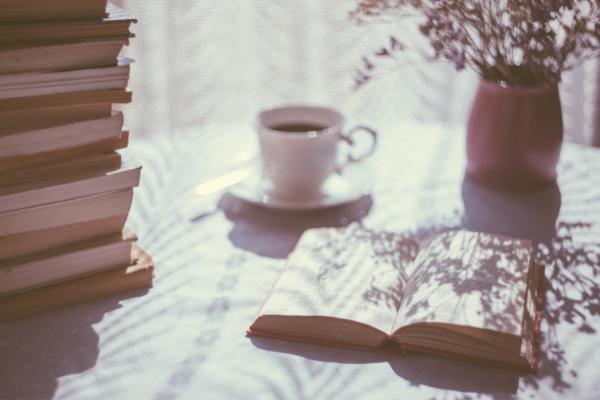 a cup of tea sits on a table covered in a white cloth by a sunny window. A stack of booksis also on the table.