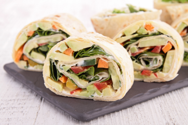 Tortilla sandwich wraps with cheese and fresh vegetables rolled and sliced in circles