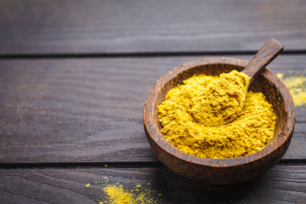 A wooden bowl of nutritional yeast on a tabletop. The yeast is a mustard yellow color and in thin flakes
