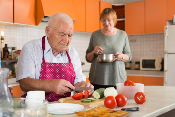 an older couple prepare a meal together in the kitchen. The woman stirs a pot and the man slices tomatoes