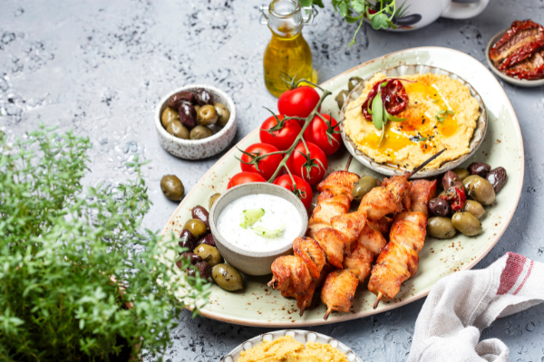 a platter contaiing olives, cherry tomatoes, chicken souvlaki skewers, hummus and tzatziki