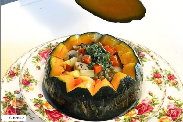 a leafy green vegetable stir fry servved inside a hollow kabocha squash with scalloped edges on a floral china plate
