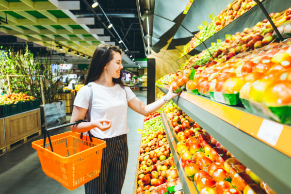 the produce aisle of a grocery store. A woman in a white tshirt and black pants holding an orange basket is selecting an apple