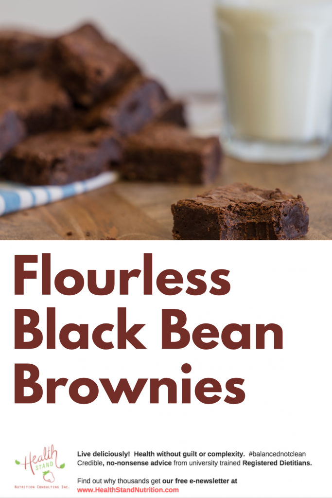 dark chocolate brownies stacked on a plate beside a tall glass of milk