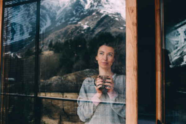 a woman stands at a window holding a cup of tea. THe mountaints and trees are reflected in the window