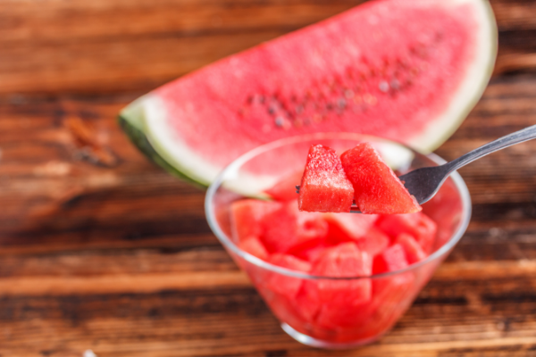 a quarter of a watermelon sits next to a bowl of cubed watermelon