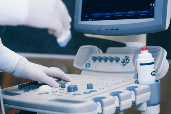 an ultrasound machine being operated by a person wearing a latex glove