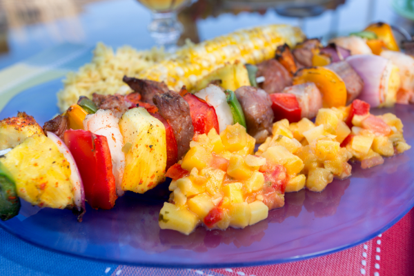 a picnic table outdoors with iced tea in glasses, a plate of watermelon, and a plate with a tropical salsa, shrimp skewers with mango and vegetables and corn on the cob