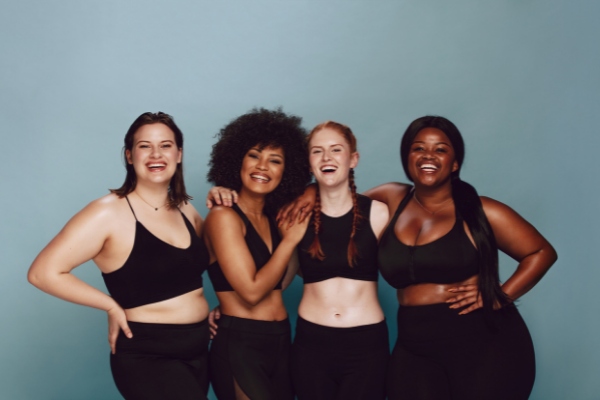 four dwomen of diverse skin colors and shapes wearing black sports bras and leggings