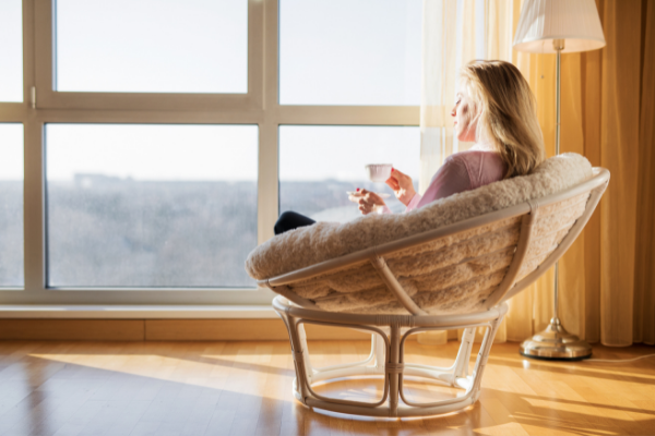 A woman sits in a round cushioned chair with a cup of tea looking out the window at a sunset