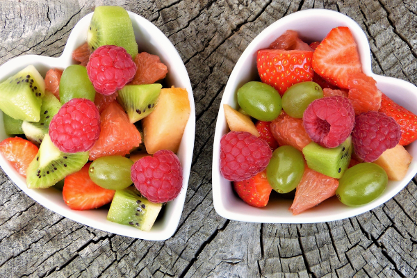 Two white heart shaped bowls filled with fruit salad including raspberries, kiwi and strawberries