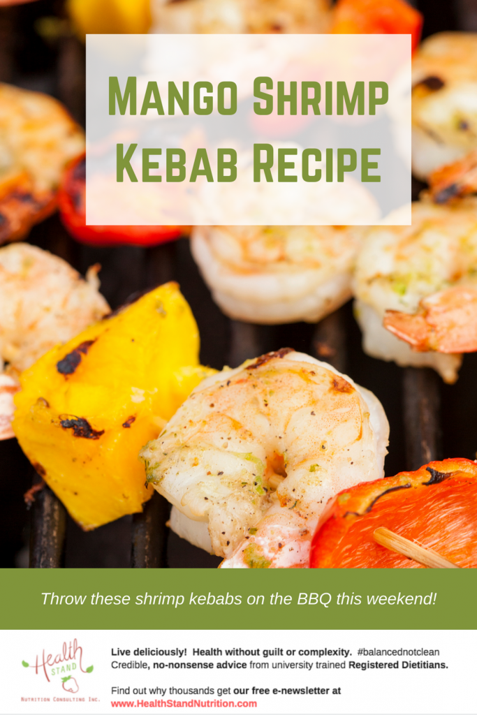 mango pieces, shrimp and red pepper on a skewer grilling on a bbq