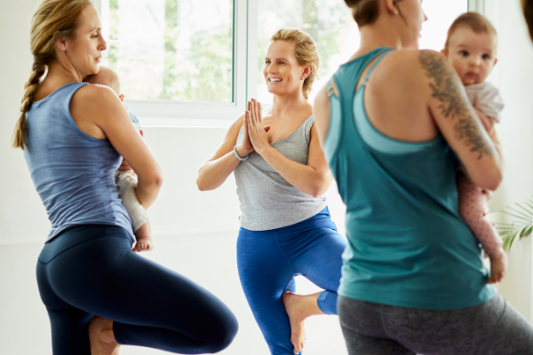 women hold their infants while doing tree post in yoga class