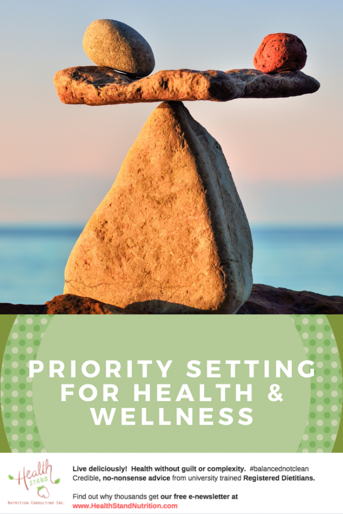 a triangular rock sits on a beach with a flat stone and two smaller round stones balanced on top of it