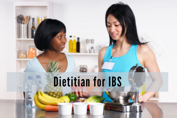 A dietitian wearing a blue tank top and a name badge talks with a black woman while various foods and a scale are laid out in front of them