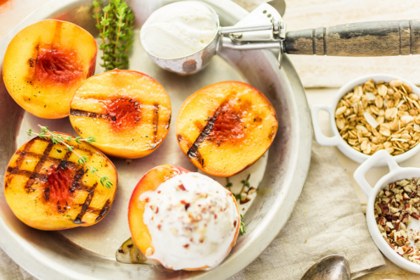 grilled peach halves on a platter with a scoop of ice cream and some sprinkled with toasted coconut