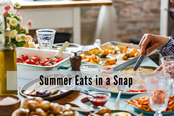 an outdoor table with food for sharing including fruit salad, a tomato tart and vegetables