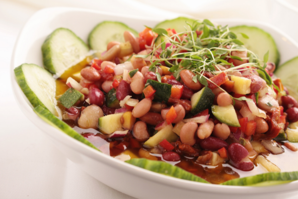 a mixed ben salad in a white bowl ringed with cucumber slices and topped with sprouts